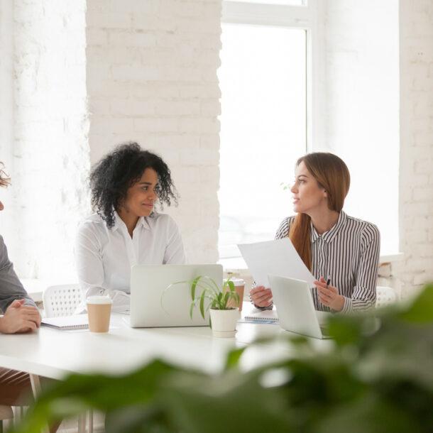 Comunicação colaborativa: colegas de trabalho compartilham ideias sentados ao redor de uma mesa em uma sala.