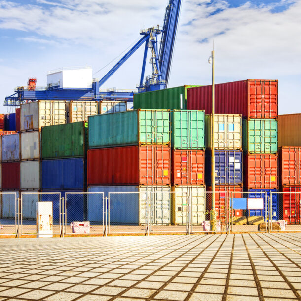Gestão de logística internacional: containers coloridos empilhados em um terminal.