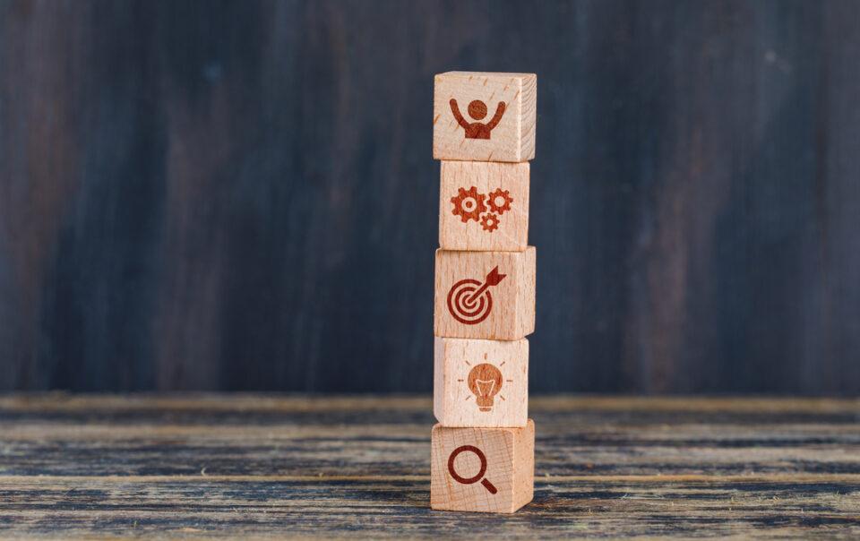 Gestão integrada: pequenos cubos de madeira empilhados e gravados com símbolos.