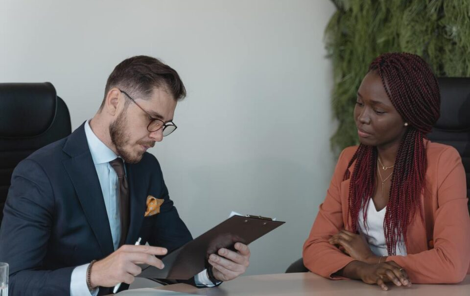 RH estratégico: homem vestindo roupas sociais entrevista uma mulher que está à sua frente. Ambos estão apoiados em uma mesa.